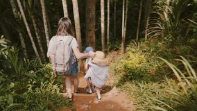 Camera follows happy young mother together with two little children walking down a steep exotic forest path slow motion. stock video