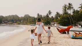 Camera follows happy young mother with two little children walking along exotic beach on tropical vacation slow motion. stock video footage