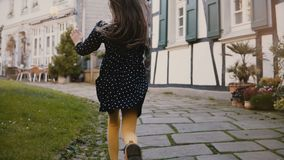 Camera follows little girl running on paved road. Back view. Ancient half-timbered houses in Hattingen, Germany. 4K. Camera follows little girl with long hair stock footage