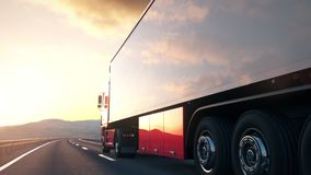 Semi-trailer truck driving along a desert road into the sunset. The camera follows a semi truck driving along a desert highway into the sunset. Low angle rear stock footage