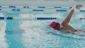 Camera follows strong female swimmer in the pool. She swims in swimsuit, swim cap and protective colorful goggles. She. Wear waterproof smartwatch on her hand stock video
