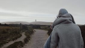 Camera follows thoughtful tourist woman in winter clothes walking towards far away overcast beach lighthouse slow motion stock video footage