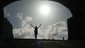Camera follows a woman silhouette walking out from tunnel towards the sunlight. Burst of bright light. Raising arms in stock footage