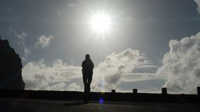 Camera follows a woman silhouette walking out from tunnel towards the sunlight. Burst of bright light. Raising arms in. Air stock video footage