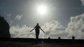 Camera follows a woman silhouette walking out from tunnel towards the sunlight. Burst of bright light. Raising arms in