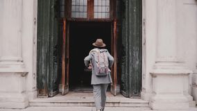 Camera follows young fashionable female tourist walking into San Marco cathedral doors in Venice, Italy slow motion. Camera follows young fashionable female stock video