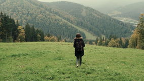 Camera follows young girl hiker walking outdoors on background of mountain landscape. Outdoor activity. Lifestyle adventure. Back view, toning, 4k stock video