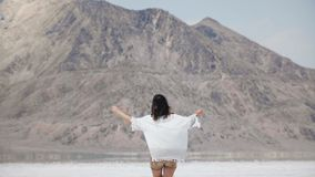 Camera follows young happy free woman walking towards mountain with arms open and flying hair at salt desert lake Utah. stock video footage