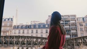 Camera follows young happy tourist woman smiling at sunny Paris balcony, pointing at epic Eiffel Tower view slow motion. stock video