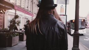 Camera follows young local girl in leather jacket and stylish hat walking along a city street slow motion, bus at a stop