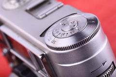 Camera. A fragment of an old metal camera on red. Stock Images