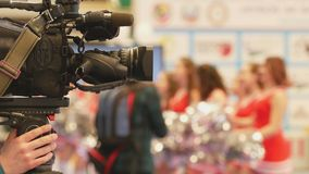 Camera in front of girls cheerleaders at the karate championship royalty free stock photography