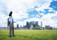 Camera geleide mens die zich op groen gras tegen moderne cityscape bevinden Stock Fotografie