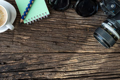 Camera, glasses and notepad on wood,above view royalty free stock photo