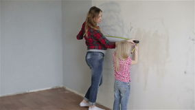 Camera goes down. Mother and daughter measuring wallpaper. Camera goes down. A pregnant mother and a small daughter measuring place for the next part of stock video