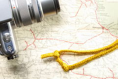 Camera and gold rope on map Royalty Free Stock Photos