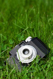 Camera in the grass. A photo of an old Cmena film camera in on the ground in a green grass Stock Photo