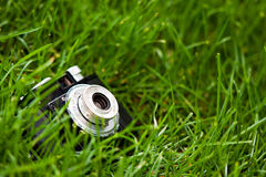 Camera on the ground. A photo of an old Cmena film camera in on the ground in a green grass Stock Photography