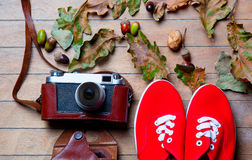 Camera and gumshoes. Photo of retro camera and gumshoes on wooden table full of foliage, acorns and nuts Stock Photos