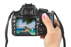 Camera in hand and beach landscape Royalty Free Stock Photos