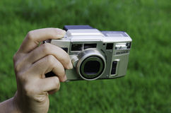 Camera. Hand holding the camera with grass in the background Stock Photography