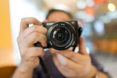 Camera in hand. A photographer is holding a camera shooting photos Royalty Free Stock Image
