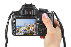 Camera in hand and Santorini (Greece) view Royalty Free Stock Photo
