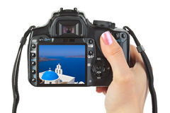 Camera in hand and Santorini (Greece) view Royalty Free Stock Photos