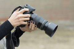 Camera in the hands of a girl Stock Photos