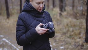 Camera in the hands of the photographer. looks at settings and taken snapshots. autumn forest. cinematic shot, slow. Motion stock video footage