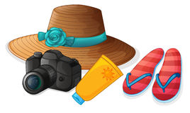 A camera, a hat, a lotion and a pair of slippers Stock Image