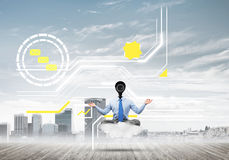 Camera headed man sitting in lotus pose on cloud against modern cityscape Royalty Free Stock Images