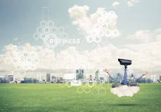 Camera headed man sitting in lotus pose on cloud against modern Royalty Free Stock Image