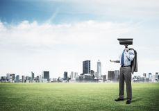 Camera headed man standing on green grass against modern citysca Royalty Free Stock Images