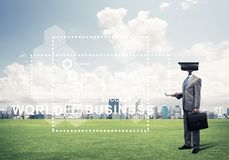 Camera headed man standing on green grass against modern citysca. Elegant businessman outdoors with camera instead of head and media interface on screen Stock Images