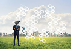 Camera headed man standing on green grass against modern citysca Stock Image