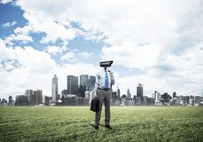 Camera headed man standing on green grass against modern citysca. Elegant businessman outdoors holding jacket on shoulder and camera instead of his head Stock Photos