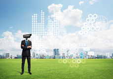 Camera headed man standing on green grass against modern cityscape Stock Photos
