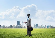 Camera headed man standing on green grass against modern cityscape Stock Image