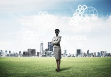 Camera headed woman standing on green grass against modern citys Royalty Free Stock Photo