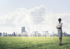 Camera headed woman standing on green grass against modern citys Royalty Free Stock Images