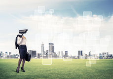 Camera headed woman standing on green grass against modern citys Stock Photography