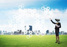 Camera headed woman standing on green grass against modern cityscape Royalty Free Stock Image