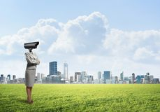 Camera headed woman standing on green grass against modern cityscape Royalty Free Stock Photo