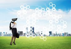 Camera headed woman standing on green grass against modern cityscape. Elegant businesswoman outdoors with camera instead of head and media interface on screen Royalty Free Stock Photos