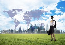 Camera headed woman standing on green grass against modern cityscape Stock Image