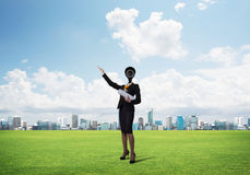 Camera headed woman standing on green grass against modern cityscape Royalty Free Stock Images