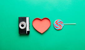 Camera, heart shaped box and lollipop. Photo of retro camera, heart shaped box and colorful tasty lollipop on the wonderful green studio background Royalty Free Stock Photo