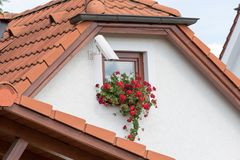 Cesky Krumlov, Czech Republic - August 17, 2017. Camera installed on a wall of a home with a small window and flowers Royalty Free Stock Image