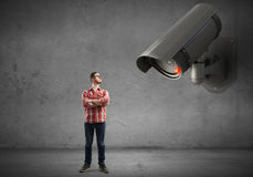 Camera keep an eye on man . Mixed media Royalty Free Stock Photo